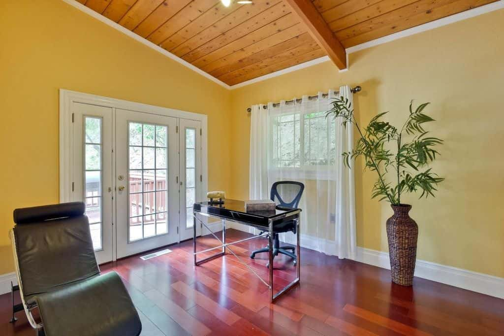 Yellow home office showcases a black metal office desk with mesh chair accompanied by an indoor plant and black chaise lounge over cherry hardwood flooring.