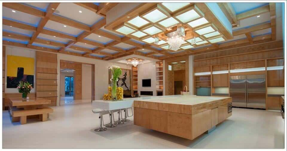 Large modern kitchen interior design with patterned wood beam ceiling and large island with a separate white eat-in counter.