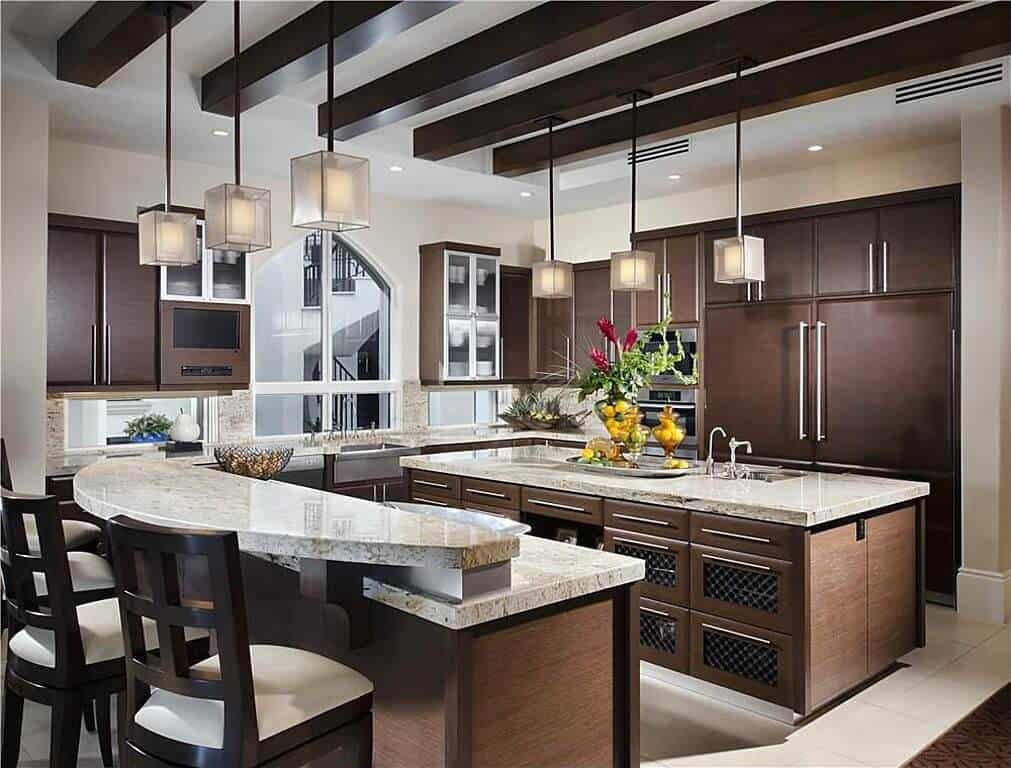 This kitchen features a two-tier breakfast counter that sits beside the kitchen island illuminated by cube pendants that hung from the wood beam ceiling.