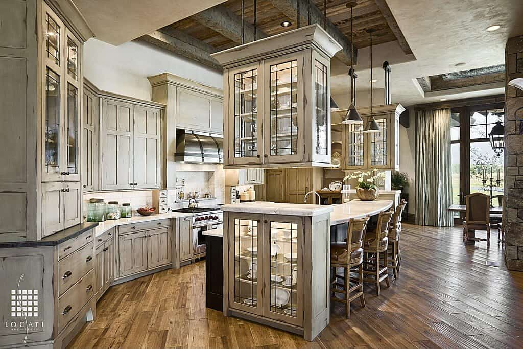 This kitchen is filled with distressed white cabinetry and a breakfast island with glass front cabinets on its end. It is illuminated by black pendants that hung from the wood beam ceiling.