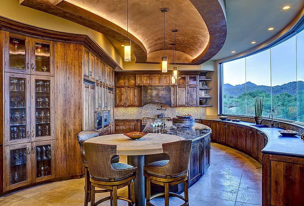 Sophisticated kitchen boasts rustic cabinetry and a marble top kitchen island with a round eating counter on its end surrounded with wingback bar chairs. It includes a curved tray ceiling and panoramic window overlooking a spectacular mountain view.