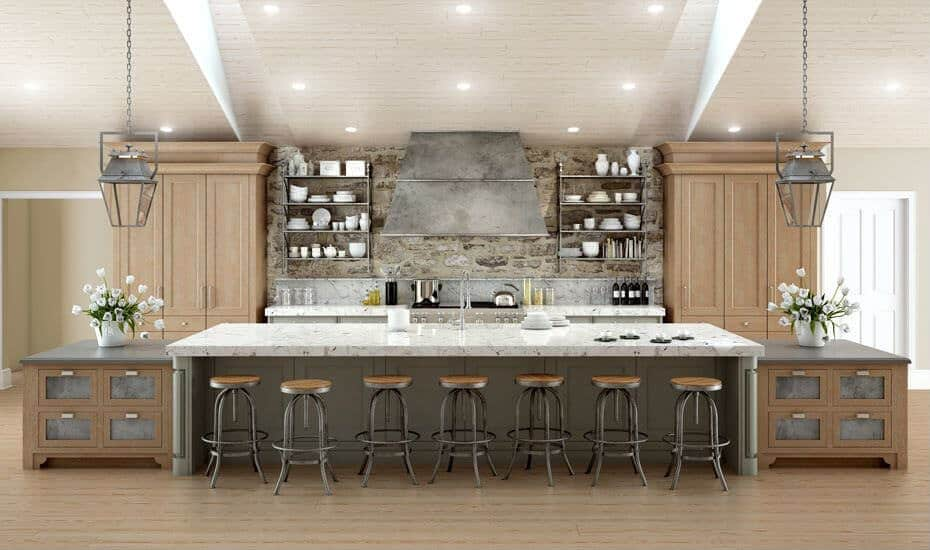 This kitchen offers a large center island with a lovely marble countertop. There's a wide space for breakfast bar lighted by two pendant lights. The backsplash of the kitchen attract eyes.