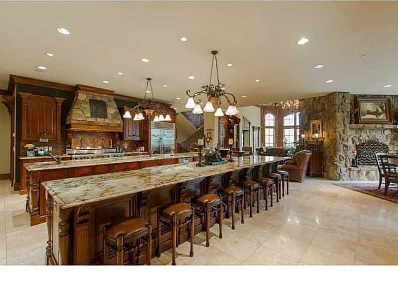 A huge kitchen offering two long center islands. The one is for preparing dishes while the other island serves as the breakfast bar for eight persons, both are lighted by cozy chandelier backed by several recessed lights.