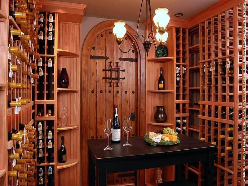 Small space with redwood storage racks and a black tasting table in the middle lighted by an iron wrought chandelier.