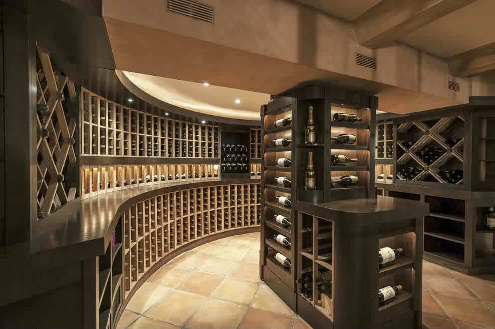 Large semi-circular design with extensive custom wood cabinets. Floor-to-ceiling cabinet forms an island in the center of the room with a display case for featuring wines.