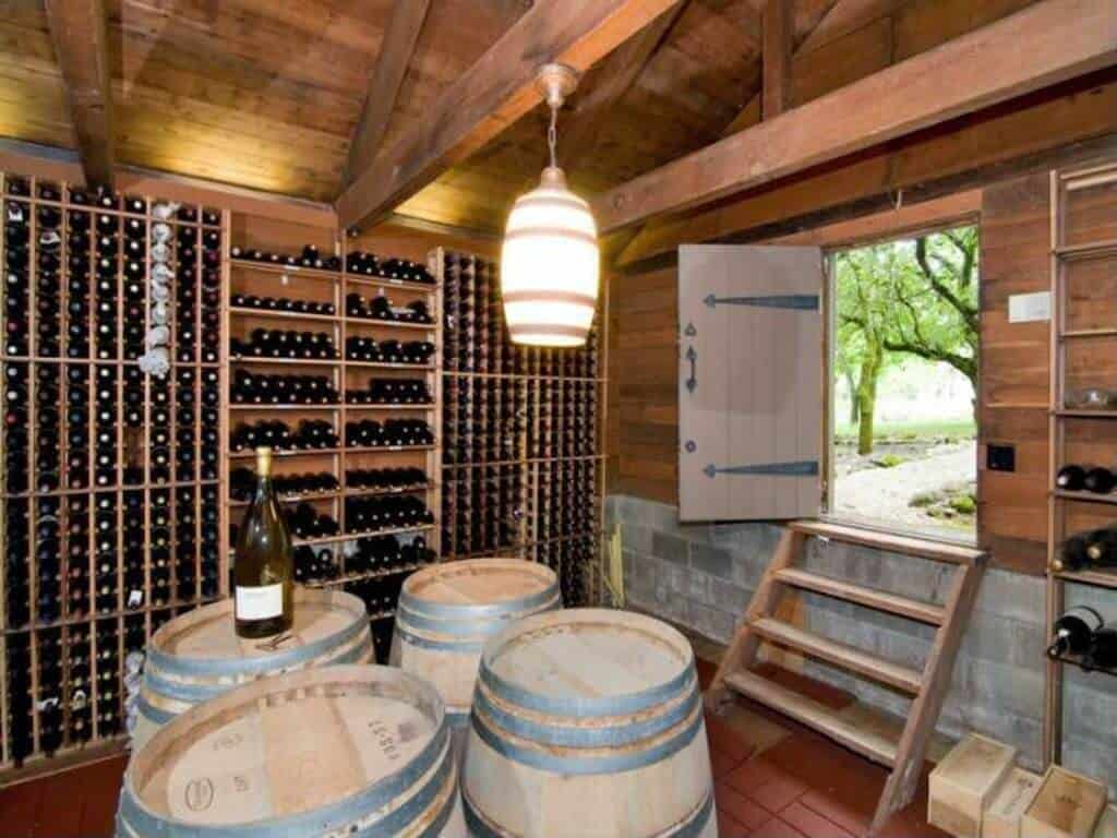 Wine cellar with matching barrel tasting table and light fixture. The notable feature of this space is the access door to the outside which is a loading door for deliveries.