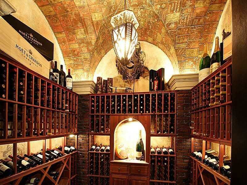 Small wine room with an intricately designed ceiling. Cabinets include display storage sections for featuring select bottles.