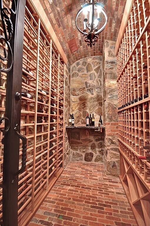 A narrow wine cellar featuring a lovely spherical candle chandelier that hung from a brick ceiling matching the floor. It has wooden racks and a countertop fixed to the stone wall.