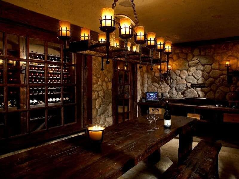 Large wine room with attractive stone walls fitted with a wood storage cabinet. An oversized chandelier hung over a rectangular tasting table.