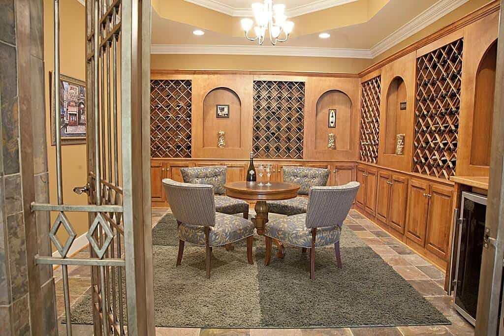 Modern tasting room designed with custom wood cabinets and a round antique table with chairs over a shaggy rug.