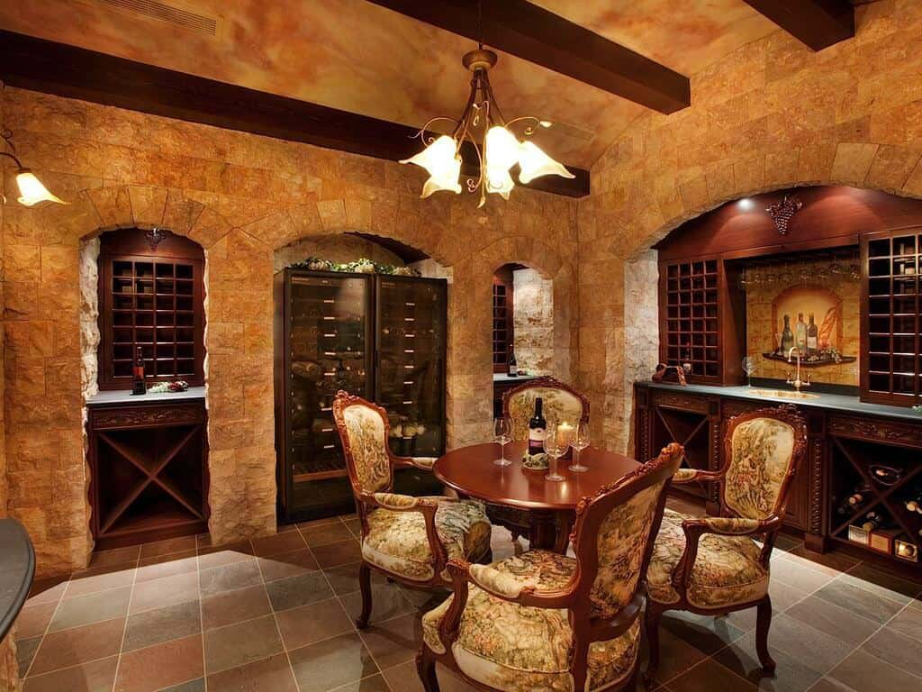 Luxurious tasting room in a cave-like design with arched brick walls along with exposed wood beam ceiling. It features a round tasting table surrounded with upholstered chairs.