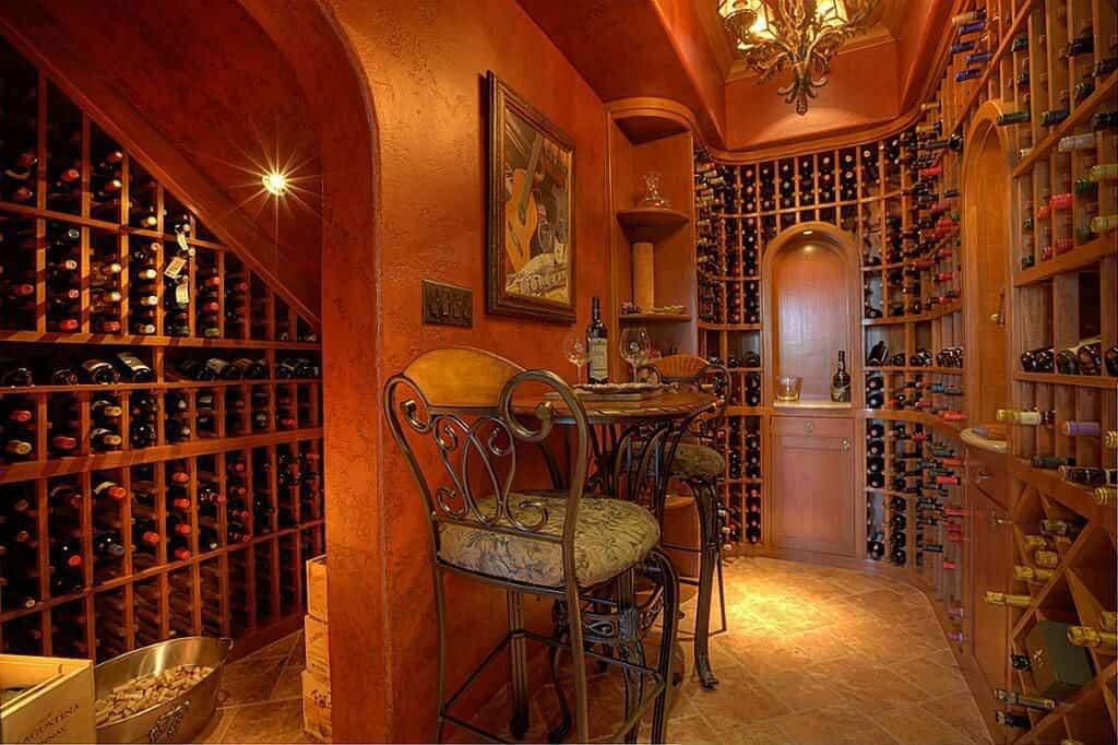 Richly designed room with chandelier, floor-to-ceiling cabinets and small tasting table for two people.