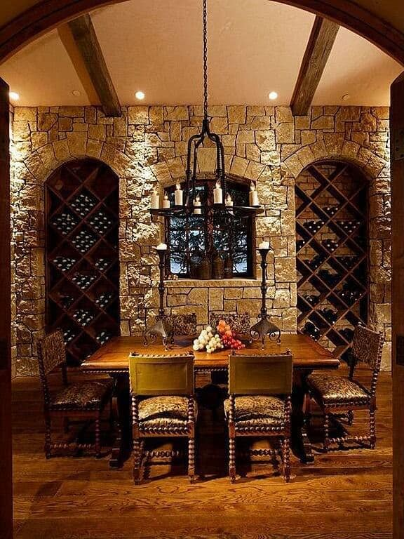 Ornate stone with exposed wood beamed ceiling and tasting table with faux leopard chairs completed by a candle chandelier.