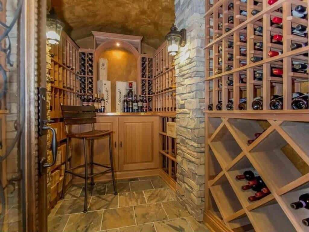 Cozy liquor storage room accented with stone pillars and designed in wood with small sitting stool and counter for tasting.