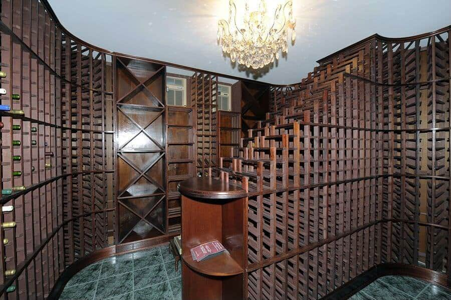 This space is capable of storing thousands of bottles in dark wood cabinets and green tile floor. It features a waterfall wine rack lighted by a fancy chandelier.