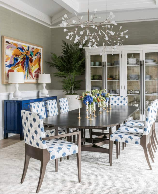 Fabulous dining room boasts a pair of unique chandeliers and colorful wall art that hung above the blue console table topped with white lampshades.