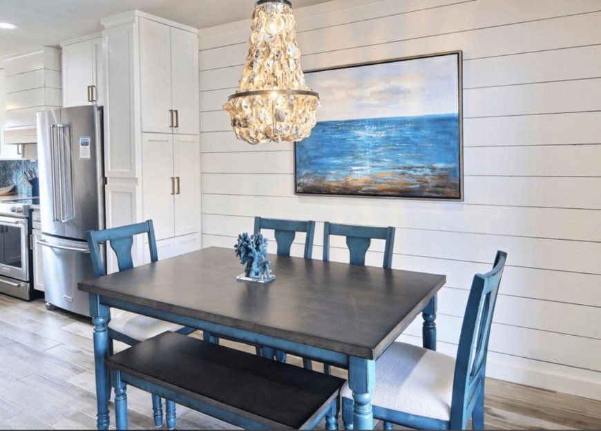 This dining room showcases a distressed blue dining set lighted by an oyster shell chandelier and a lovely beach canvas mounted on the white shiplap wall.