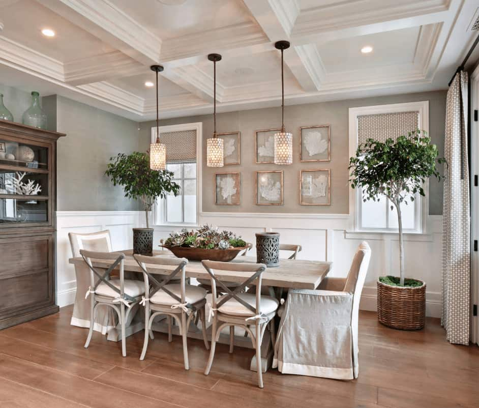 Tall potted plants bring life to this fresh dining room offering a natural wood dining table with cushioned and skirted chairs lighted by cylindrical pendants that hung from the coffered ceiling.