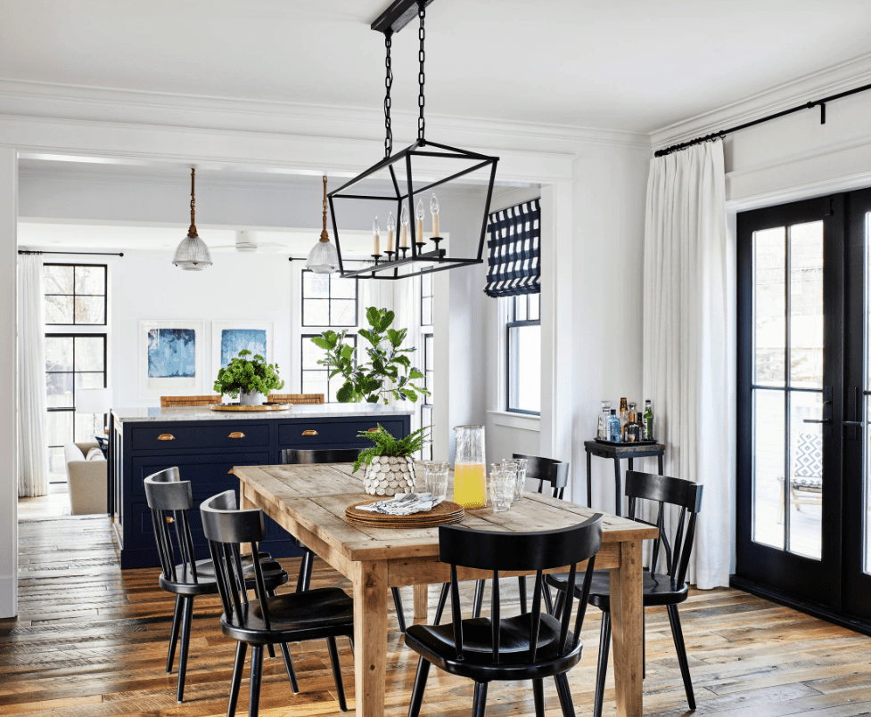 A caged chandelier illuminates this dining room featuring wood plank flooring and a double door that leads out to the balcony. It has black chairs and a natural wood dining table topped with a potted plant.