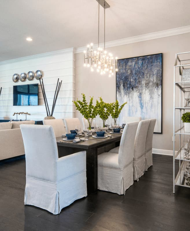 Beach dining room features an interesting abstract wall art and white skirted chairs beautifully contrasted by a dark wood dining table and wood plank flooring.