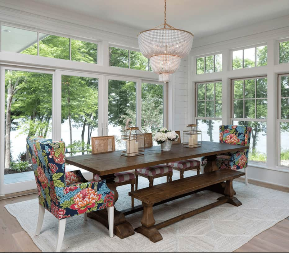Floral wingback chairs add a charming accent to this beach style dining room boasting a boho chandelier and wooden dining set surrounded with full height windows that overlook a serene outdoor view.
