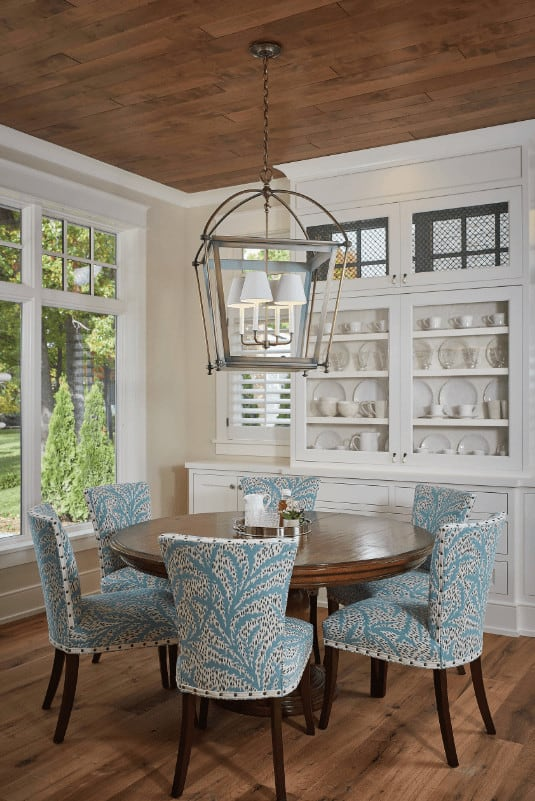 Blue printed wingback chairs stand out in this cozy dining room with white display cabinet and a round dining table lighted by an oversized caged pendant.