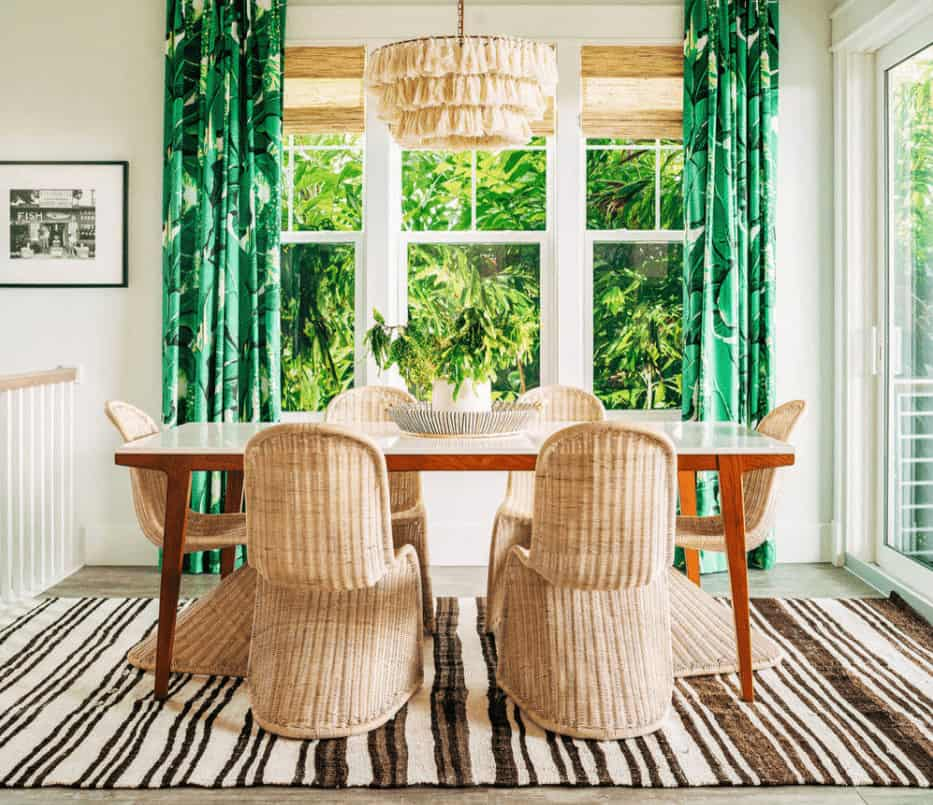 Green foliage draperies bring a refreshing accent to this beach dining room showcasing a wooden dining table and wicker chairs that sit on a striped area rug.