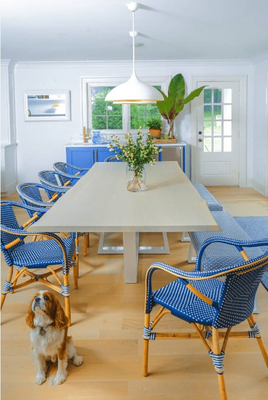 A blue storage cabinet placed beneath the white framed windows sits behind the sleek dining table and blue dotted seats lighted by a pair of dome pendants.