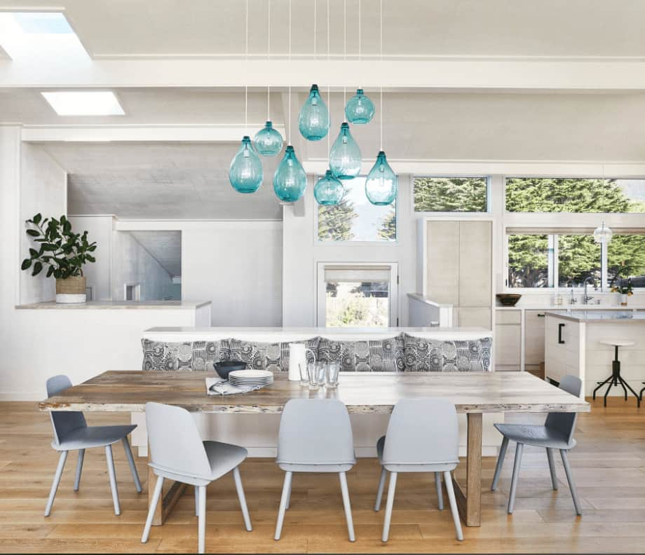 A wooden dining table complements the wood plank flooring in this open dining room offering gray seats and white bench with floral pillows lighted by translucent blue pendants.