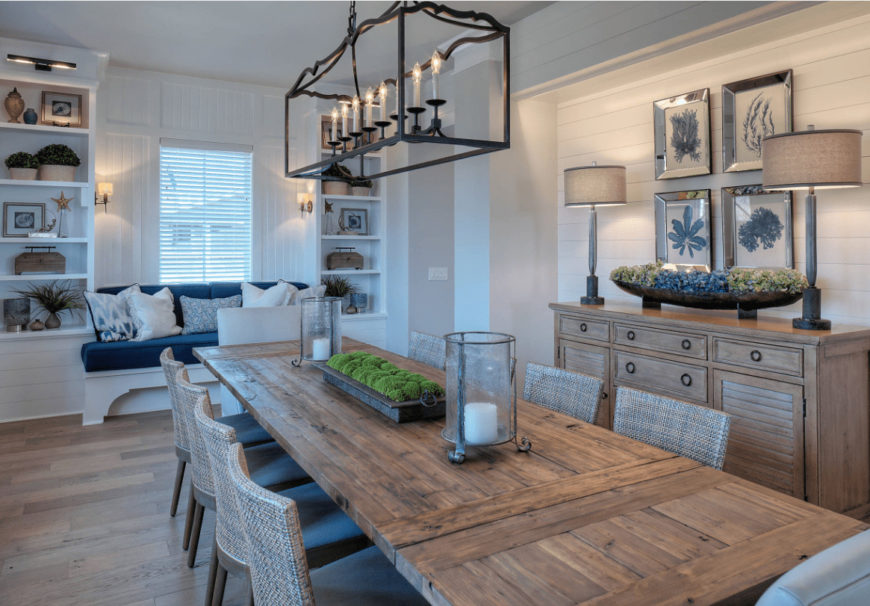 Beach style dining room features a linear chandelier and natural wood dining set that complements with the console table accented by floral wall arts. It includes a window seat nook flanked by built-in shelving and wall sconces.
