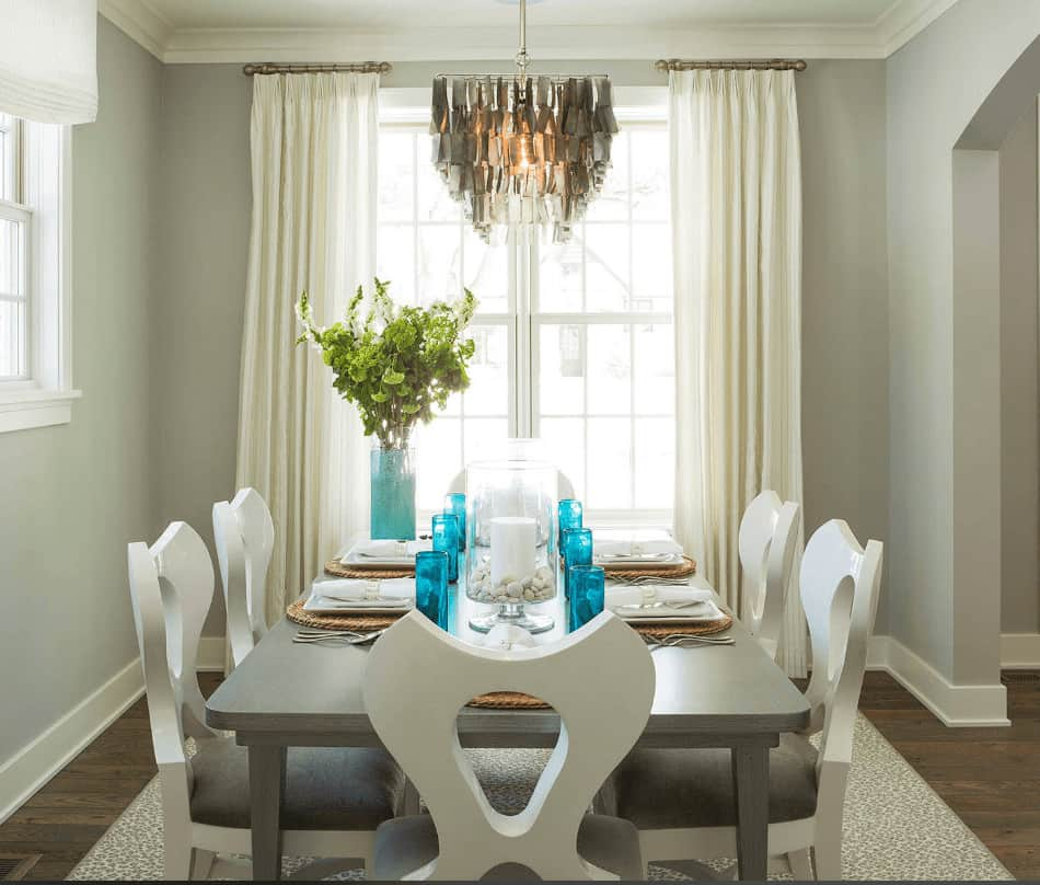 Gray dining room with glazed windows and dark wood plank flooring topped by a printed area rug. It has a rectangular table and stylish cushioned chairs lighted by an eccentric chandelier which adds character in the room.