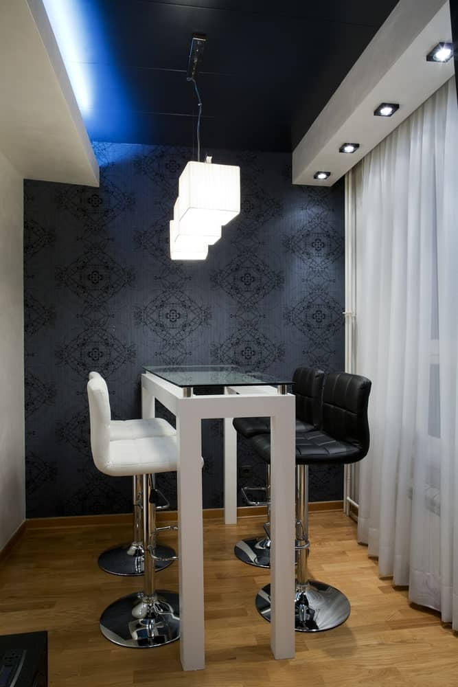 This is an intimate and simple dining room that has a tall glass-top table paired with black and white leather stools to a background of black patterned walls and black ceiling.