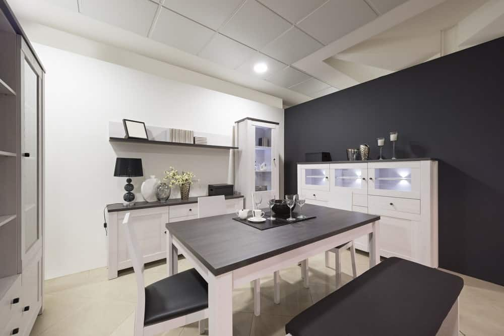 This simple black and white dining room have smooth black walls contrasted by white flooring and ceiling. This same theme is used in the dining set that has black tops on white legs.