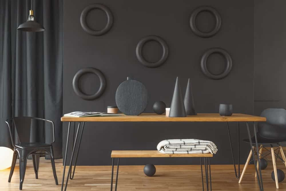 The brilliant pitch-black walls are accented with black decors that make the wooden table stand out. It has the same hue as the hardwood flooring for nice parallelism.