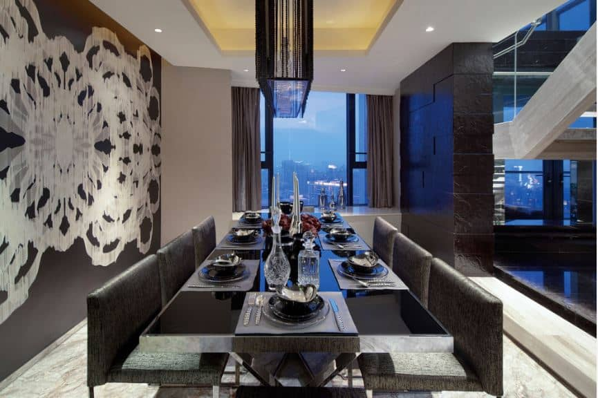 This is an extremely elegant formal dining room with a black wall on one side that is dominated by an abstract floral mural paired with another black wall made of textured black granite blocks that match the black modern dining set.