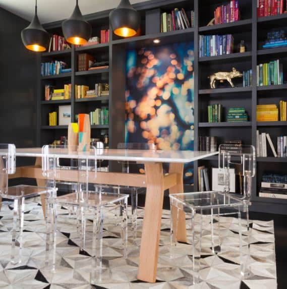 The modern plastic chairs are paired with a white-topped dining table that stands out against the black bookshelves dominating the wall by the table that is topped with a trio of black dome pendant lights.