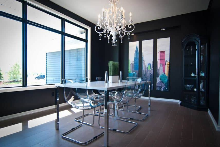 The modern plastic and white dining set with metal legs are paired with a white intricate chandelier that contrasts the black walls.