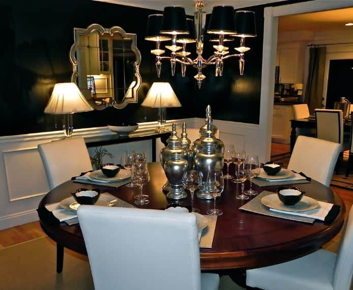 The black walls are contrasted with white wainscoting and a silvery elegant mirror that matches the silvery modern chandelier hanging over the round wooden table.