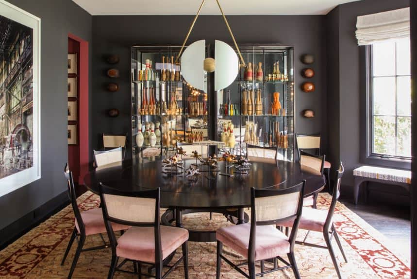 Charming pink cushioned chairs with black frames are perfectly paired with a black wooden round table that stands out against the patterned area rug.