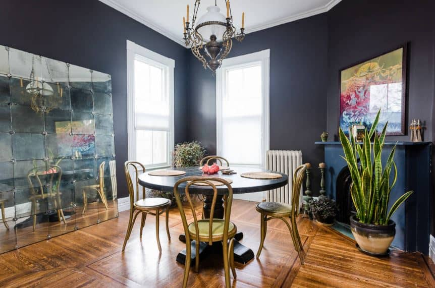 This dining room has tall white windows that illuminate the white walls and the hardwood flooring contrasted by the black wooden table beside a black fireplace.