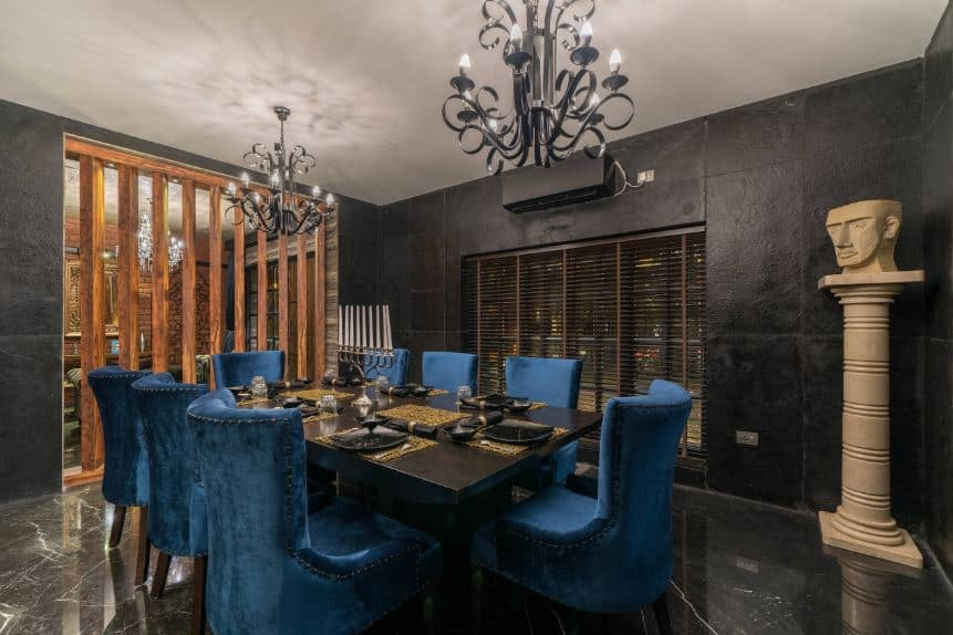 The blue velvet chairs stand out against the black marble flooring, black table, and black walls that are adorned with a beige pillar bearing a head figure at the top.