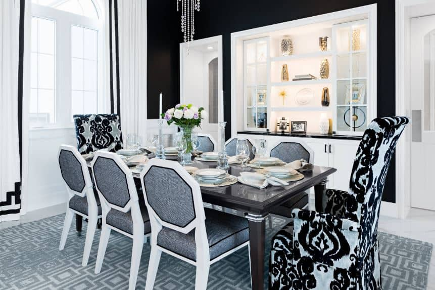 This is a bright dining room with a delicate balance of white and pitch black elements. Black walls are paired with tall windows and the dining set has a couple of armchairs with floral black patterns at each head of the table.