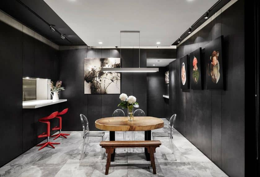 Lovely paintings of babies adorn the black walls of this dining room that has an informal dining set of a wooden table, bench, and modern plastic chairs.