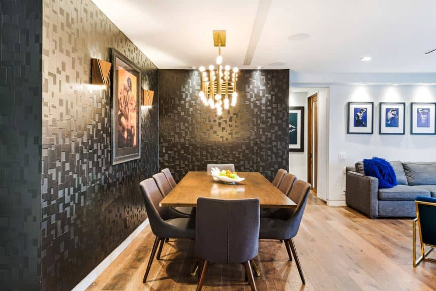 The textured patterns of the black walls of this dining area is a nice background for the white ceiling, long wooden dining table, and surrounding gray chairs.