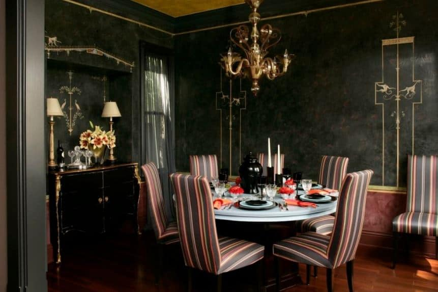 There are colorfully striped Parsons chairs surrounding the white round table that stands out against the black walls of this dining room topped with an elegant golden chandelier that matches the golden details of the walls.