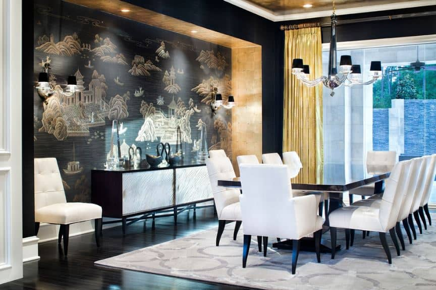 The black wall with oriental designs is lit within a golden alcove by wall-mounted lamps. This wall is a nice contrast for the white leather chairs surrounding the black dining table.