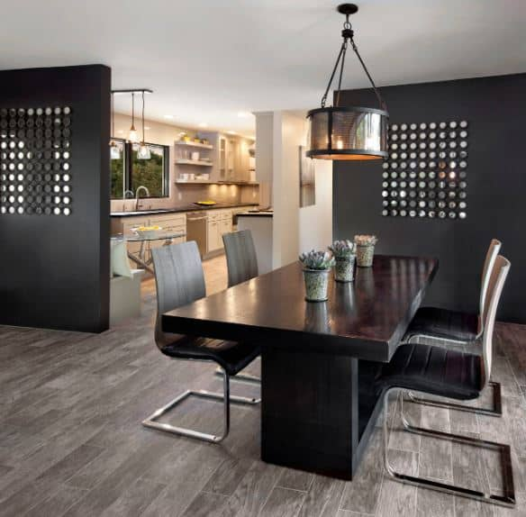 The black modern table paired with modern black leather dining chairs match the black panels with decorative holes that act as dividers for this dining room and the rest of the home.