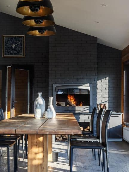 The white shed ceiling is contrasted by a black wall made of bricks that house a furnace and its copped wood storage. This is paired with a rustic wooden table and modern black chairs.