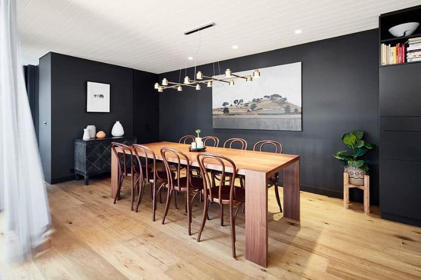The wooden table blends with the hardwood flooring that contrasts with the wooden pitch-black walls accented with wall-mounted borderless photos.