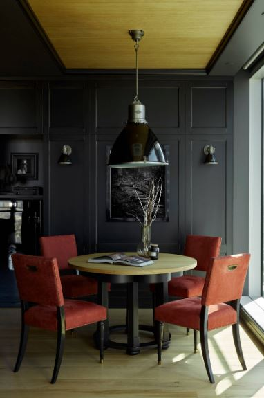 The wooden round table surrounded by red cushioned dining chairs stands out against the black walls and black tray ceiling that has a wooden tray center that supports a large black dome pendant light.